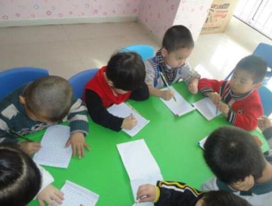 初学握笔写字的幼儿园小朋友